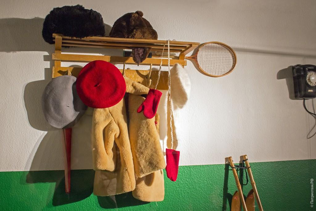 Вешалка с одеждой и предметами советских времен.