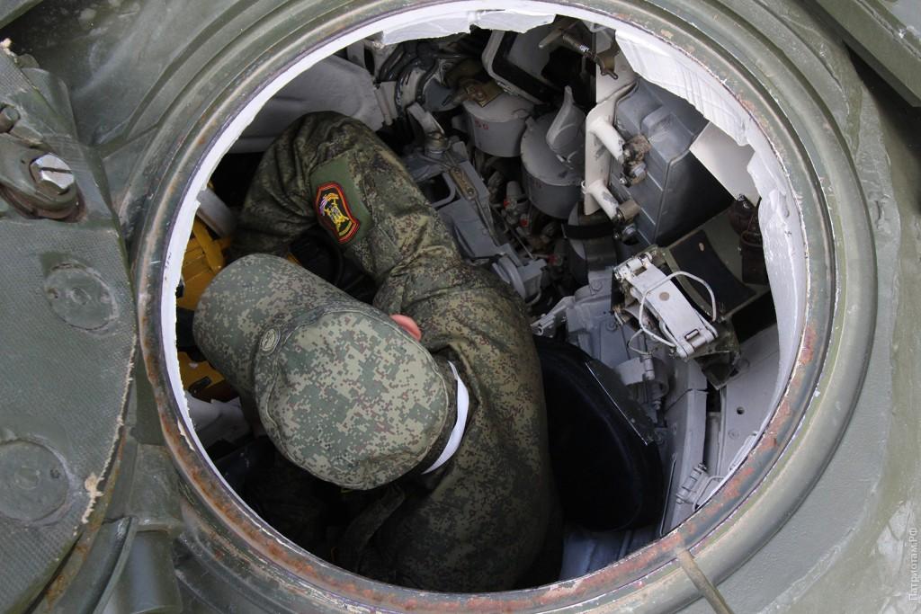 Солдат что-то чинит в танке после кривых рук посетителей.
